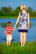 young woman and baby boy holding hands on lake