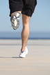 Unfocused man legs running on the concrete of a seafront
