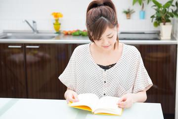 部屋で本を読む女性