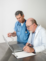 Two Senior Doctors at Laptop Computer Talking