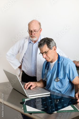 Two Senior Medical Doctors Discussing Patient's MRI Film Scans