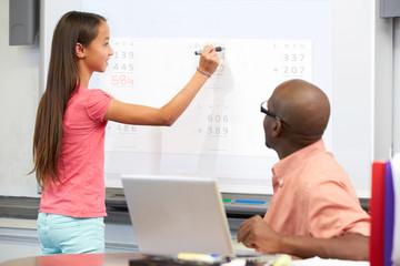 Female Student Writing Answer On Whiteboard