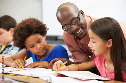 canvas print picture Teacher Helping Pupils Studying At Desks In Classroom