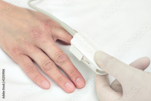 Doctor in a glove puts the sensor on patient's finger. Symbol of