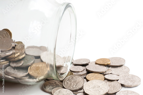 Australian coins spilling out of a glass jar