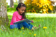 canvas print picture - Outdoor portrait of a cute young black little girl reading a boo