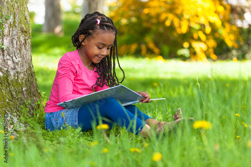 Outdoor portrait of a cute young black little girl reading a boo - 52160502
