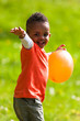 Outdoor portrait of a cute young  little black boy playing with