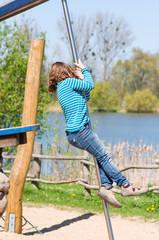 Kind klettert an der Stange
