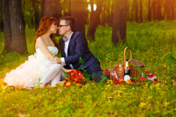couple sunlight bride and groom sitting on the green grass, a pi