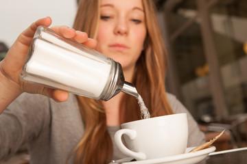 Junge Dame gießt Zucker in Kaffee Tee Tasse