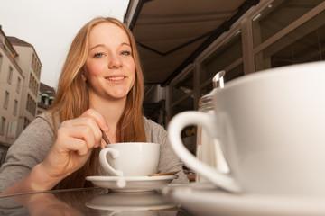 Junge Dame rührt Kaffee / Tee um