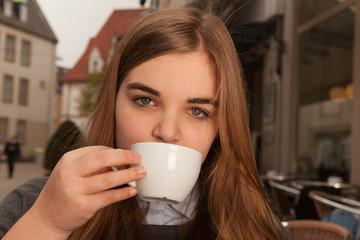 Junge Frau trinkt Kaffee / Tee