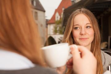 Junge Dame trinkt aus Kaffeetasse gegenüber ihrer Freundin