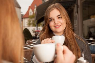 Junge Dame hält Kaffeetasse und lächelt
