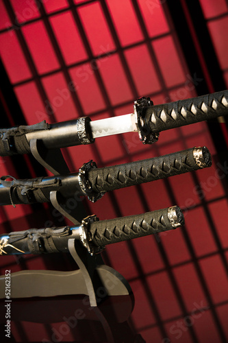 Drawn katana with other swords on red background