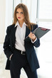 Businesswoman in man's suit & shirt at her office fashion styled