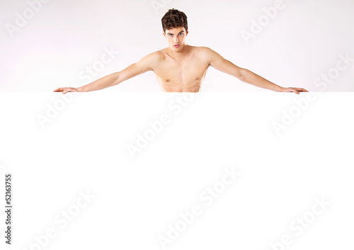 Muscular nude man behind big empty board