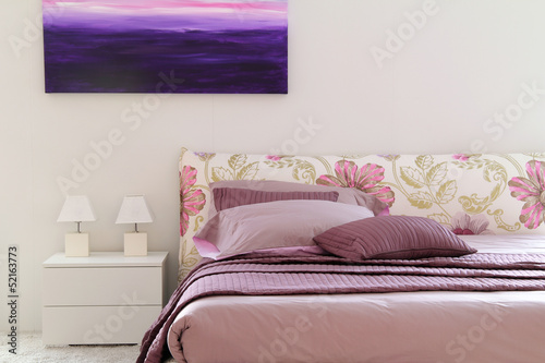Stylish purple and pink bed in white bedroom