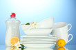 empty clean plates and cups with dishwashing liquid and lemon