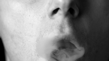 Man blowing smoke rings in black and white