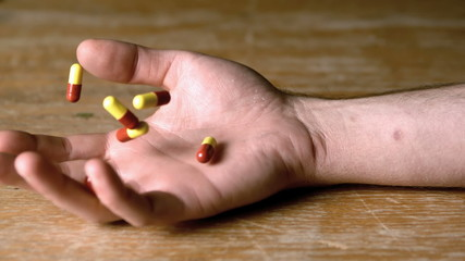Mans hand falling holding pills after overdose