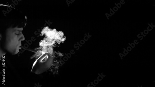 Man lighting cigarette on black background