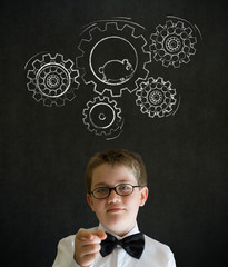 Boy dressed as business man with chalk turning gear cogs