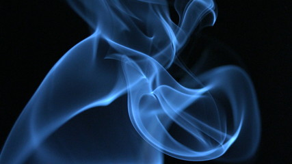 Blue smoke rising on black background