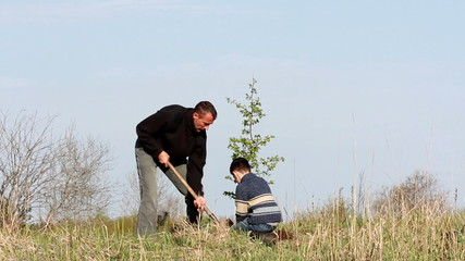 Father and son planting a tree.