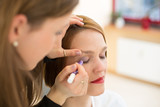 Cosmetician applying eye makeup poster