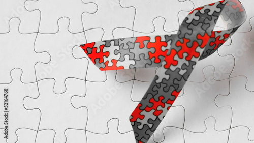 Autism ribbon falling onto jigsaw surface in selective black and white