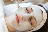 Cosmetician giving client facial skincare mask poster