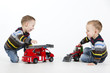 Twin brothers playing with toy fire engine in studio.