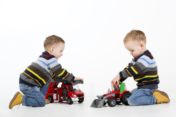 Twin brothers playing with toy fire engine and car