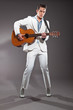 Retro rock and roll male guitar player wearing white suit. Studi