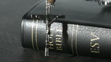 Rosary beads falling onto a bible