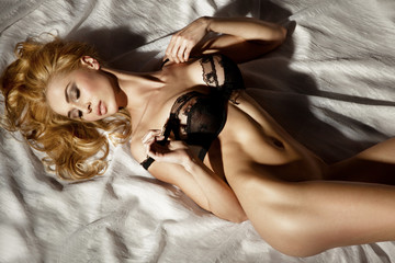 Sexy blonde lady lying in sensual pose.