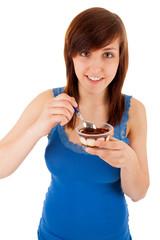 Die junge Frau isst eine Süßspeise aus einem Plastikbecher