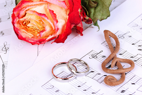 Treble clef, roses and wedding rings on musical background