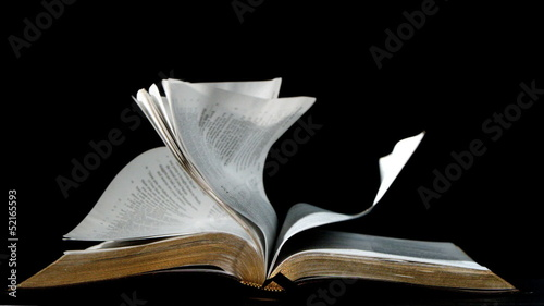 Pages of the bible turning in the wind on black background