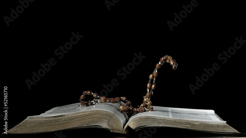 Rosary beads falling onto open bible on black background
