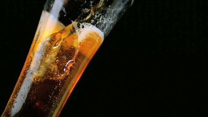 Beer pouring into glass on black background