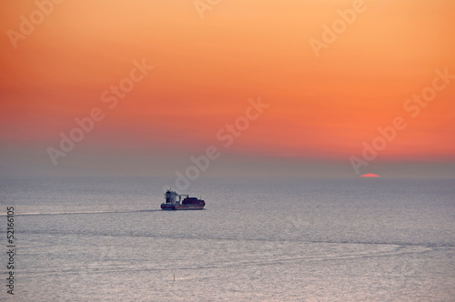 cargo ship in sea at the sunset
