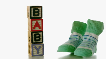 Green slippers falling besides baby blocks