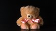 Teddy bear with pink ribbon falling on black background