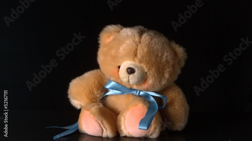 Cute teddy bear falling on black background