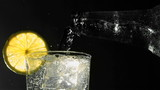Bottle pouring water into glass with ice and lemon wedge