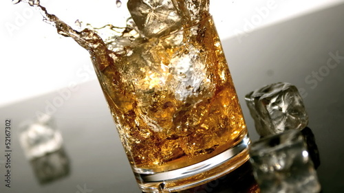 Ice falling into tumbler of whiskey and ice