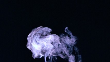 Rising puff of smoke on black background
